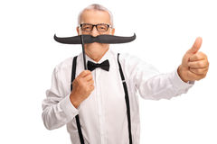 Elderly gentleman with big fake moustache and a thumb up Royalty Free Stock Photography