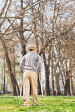 Elderly gentleman with crutches, walking in park Stock Photo