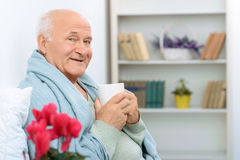 Elderly gentleman grins happily while resting Stock Images