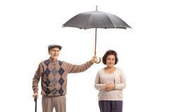 Elderly gentleman holding an umbrella over an elderly lady. Isolated on white background stock photos