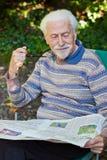 Elderly gentleman reading the paper. Elderly gentleman reading the newspaper outside in the garden Royalty Free Stock Image