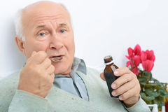 Elderly gentleman takes in his cough syrup. It does not taste well. Aged patient takes in some of the cough syrup and does not look happy about it Stock Image