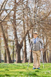 Elderly gentleman walking with crutches outdoors Royalty Free Stock Photography