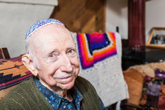 Elderly Gentleman with Yarmulke. Elderly gentleman in green vest and yarmulke seated in his livingroom Stock Images
