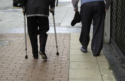 Elderly gentlemen with cane. Older gentlemen with walking stick and crutches, health stock photos