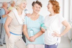 Elderly girlfriends in gym. Happy elderly active girlfriends gossiping in a gym royalty free stock image