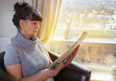 Elderly good looking woman reading newspaper. Portrait in domestic interior Royalty Free Stock Photo