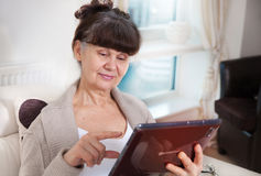 Elderly good looking woman with tablet. Portrait in domestic interior Royalty Free Stock Photo