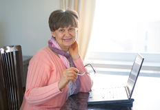 Elderly good looking woman working on laptop Royalty Free Stock Images