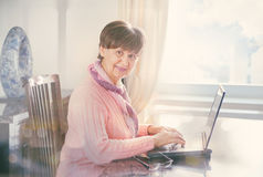 Elderly good looking woman working on laptop. Portrait in domestic interior Stock Image