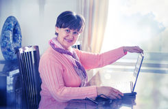 Elderly good looking woman working with laptop. Royalty Free Stock Images
