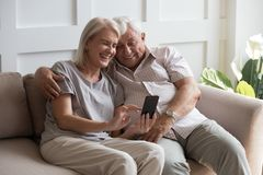 Free Elderly Grandfather And Grandmother Spend Time Having Fun Using Smartphone Stock Images - 160978864