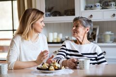 An elderly grandmother with an adult granddaughter sitting at the table at home, eating cakes. Portrait of an elderly grandmother with an adult granddaughter at royalty free stock images