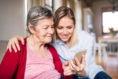 Free Elderly Grandmother And Adult Granddaughter With Smartphone At Home. Royalty Free Stock Images - 115147999