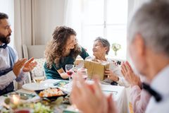 An elderly grandmother celebrating birthday with family and recieving a gift, party concept. An elderly grandmother celebrating birthday with family and royalty free stock images
