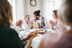 An elderly grandmother celebrating birthday with family and recieving a gift, party concept. An elderly grandmother celebrating birthday with family and stock photos