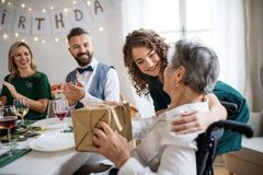 An elderly grandmother celebrating birthday with family and recieving a gift, party concept. An elderly grandmother in wheelchair celebrating birthday with royalty free stock photo