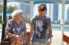 Elderly grandmother day out seaside with grandson walking beach