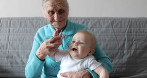 An elderly grandmother holds a small grandson in her arms and plays with him. The old woman kisses the hands of the lovely baby. 4K stock video