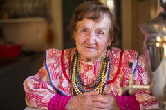 Elderly grandmother  sitting in his house. Royalty Free Stock Photos