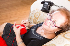 Elderly grandmother sitting knitting in a chair Royalty Free Stock Photography