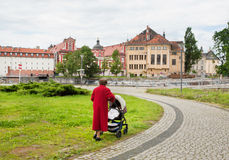 Elderly grandmother walking with baby in the stroller Royalty Free Stock Photos