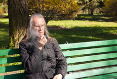Elderly gray-haired man in glasses smoking a cigarette in city p Stock Image