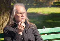 Elderly gray-haired man in glasses smoking a cigarette Royalty Free Stock Photography