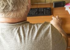 An elderly gray-haired man uses a computer mouse, work at home for the disabled, training pensioners to work on a PC, a view from. The back stock photography