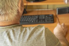 An elderly gray-haired man uses a computer mouse, work at home for the disabled, training pensioners to work on a PC, a view from. The back stock photos