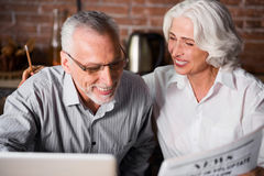 Elderly grey couple together at the laptop stock photos
