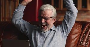 Elderly grey haired man celebrate good news read on laptop