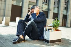 Elderly grey-haired man clutching his head while feeling panic. Clutching head. Elderly grey-haired businessman clutching his head outside the street while stock images