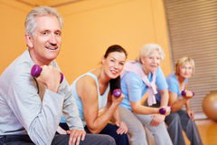 Elderly group with dumbbells in fitness center. Elderly group doing senior sports with dumbbells in fitness center Royalty Free Stock Photos