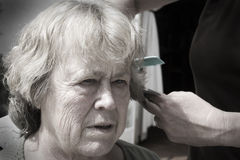 Elderly hair cut. Old lady getting her hair cut - low saturation giving the image an older feel Royalty Free Stock Photo
