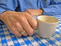 Elderly hand with coffee cup. Elderly man holding on to coffee cup royalty free stock photo
