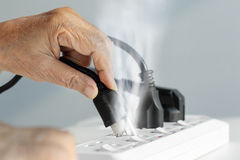 Elderly hand with electrical outlet spark royalty free stock photo