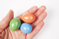 Elderly hand holding three colorful Easter eggs. Stock Image