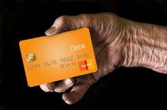 An elderly hand holds a debit card in this illustration stock image