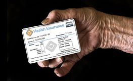 An elderly hand holds a Medicare Supplement insurance ID card stock photography