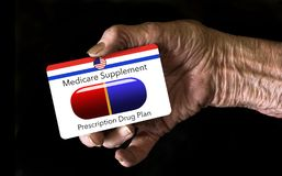 An elderly hand holds a Medicare Supplement insurance ID card stock image