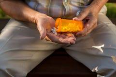 Elderly hand holds white pills. Stock Photo
