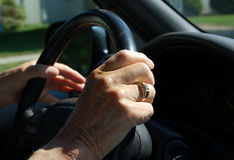 Elderly hand on steering wheel. Close-up of elderly hand on steering wheel of car stock photo