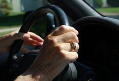 Elderly hand on steering wheel. Close-up of elderly hand on steering wheel of car Stock Photo