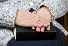 Elderly hands on bible Stock Photo