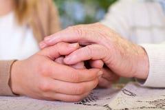 Elderly hands holding carer`s hands. Close up picture of elderly hands holding young caretaker`s hands stock images