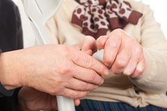 Elderly hands holding a crutch. Close up picture of old female hands holding a crutch royalty free stock images