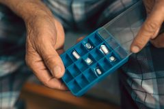 Elderly hands holding pillbox. Close up royalty free stock images