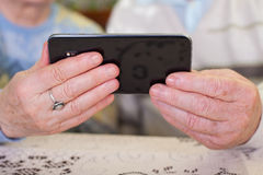 Elderly hands holding a smartphone. Close up picture of a senior couple`s hands holding a smartphone royalty free stock images