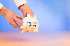 Elderly hands holding social security piggybank Royalty Free Stock Images
